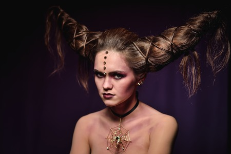Woman in Halloween makeup with hairstyle in form of horns, Devil Queen. Stock Photo
