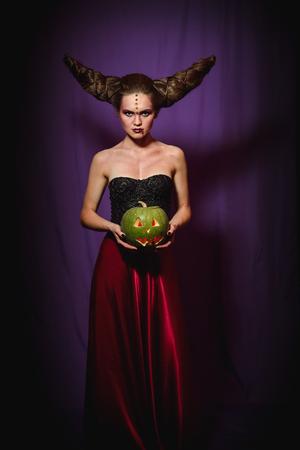 Frau in Halloween-Make-up mit Frisur in Form von Hörnern, Teufel Königin.