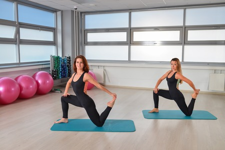 studio happy overall: Fitness, sport, exercising lifestyle - Fit women stretching in gym.