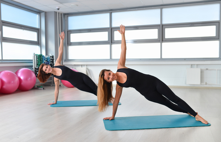Two young women doing yoga asana side plank. Vasisthasana.