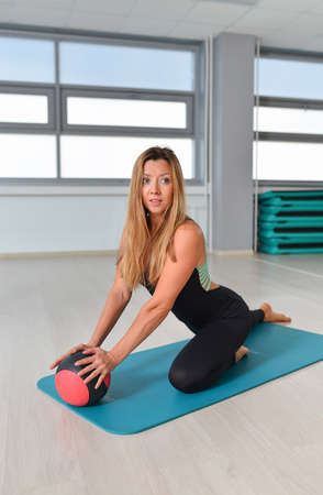 fitball: Fitness, sport, exercising lifestyle - fit woman in bodysuit posing on mat with medicine ball at gym. Stock Photo