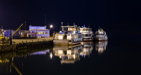 Lonely old ships on a city pier at night.