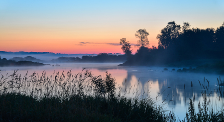 rising dead: Lake in the mist at sunrise, Misty morning landscape. Stock Photo