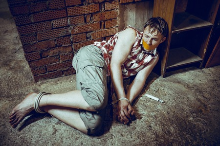 silenced: Bounded Man with mouth covered by masking tape lying in dark basement. Stock Photo