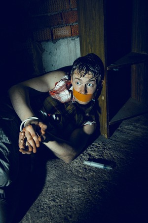 bounded: Bounded Man with mouth covered by masking tape lying in dark basement. Stock Photo