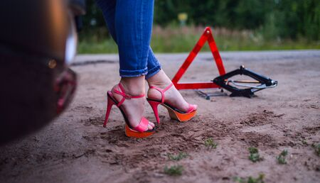 Woman standing near her broken car, warning sign triangle and jack-screw, feet closeup. Stock Photo
