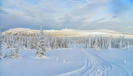 Mountain landscape with road leading to the peak in frosty winter day, Russia, Ural.