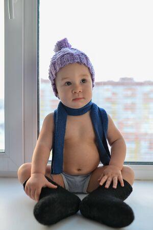 businesslike: Businesslike little baby boy comfortable sitting near the window weared in winter clothes