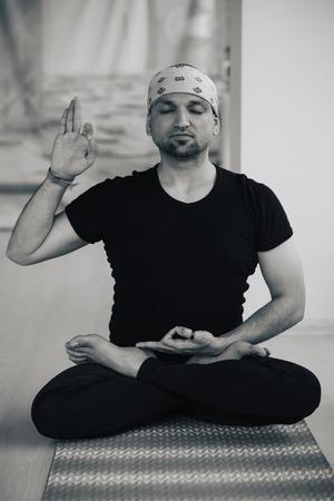 hasta: Indian man doing yoga practice indoors, full lotus meditation posture Stock Photo