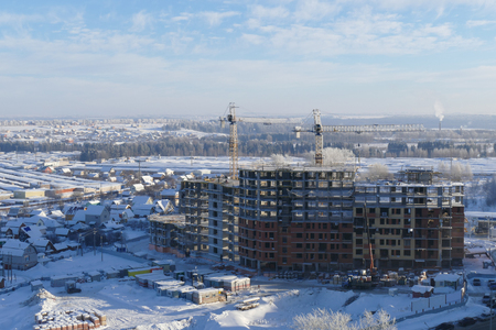 Large apartment buildings construction in new district among rural houses, urbanisation in action. Winter season. Stock Photo