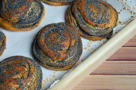 Fresh baked buns with poppy seeds on a tray on wooden background