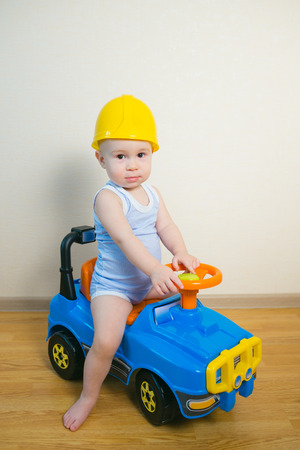 Cute Baby boy driving a toy car at home