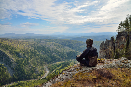 Man hiker sitting on top of mountain and contemplates beautiful view to the valley