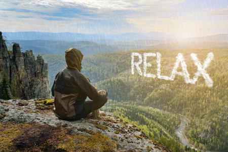 Man hiker sitting on top of mountain and contemplates beautiful view to the valley. Relax lettering in form of clouds.
