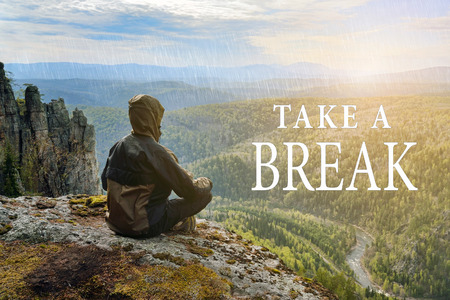 Man hiker sitting on top of mountain and contemplates beautiful view to the valley. Take a Break lettering. Banco de Imagens