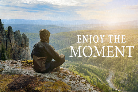 Man hiker sitting on top of mountain and contemplates beautiful view to the valley. Enjoy the Moment lettering.