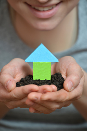 Female hands holding a piece of land with wooden house. Ecological home, construction and real estate concept. Stock Photo
