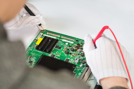 Computer repair service, hands of man tech testing motherboard with tools