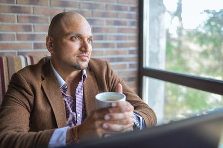 Indiase stijlvolle man koffie drinken, dromerige opzoeken en denken