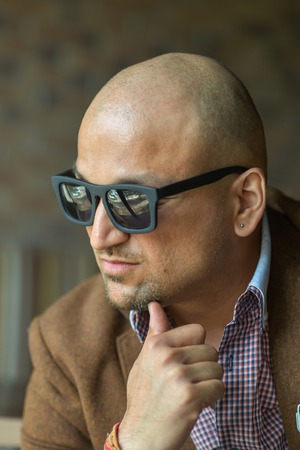 portrait of a hansome indian businessman wearing sunglasses, serious young man thinking