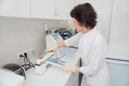 Tandartsassistent die een instrument voorbereidt voor sterilisatie in een sterilisator.