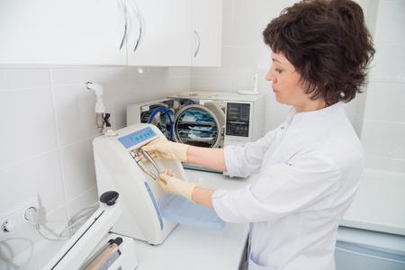 Tandartsassistent die instrumenten voor sterilisatie in de sterilisator laadt.