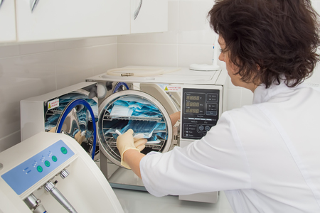 assistent: Instrument sterilization in dentistry, nurse loading instrumenst in sterilizer.