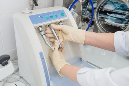 Instrumentsterilisatie en -reiniging in de tandheelkunde, verpleegster met behulp van automatische instrumentonderhoudsapparatuur om turbines en handstukken te reinigen, close-upspruit.