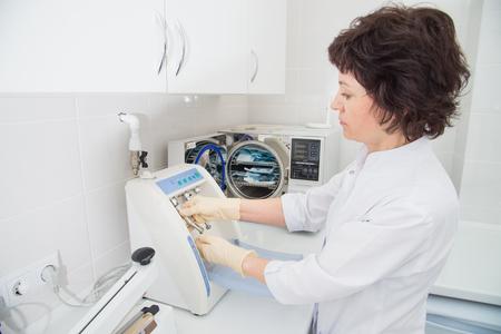 Instrument sterilisatie en reiniging in tandheelkunde, verpleegkundige met behulp van automatische instrument onderhoudsapparatuur
