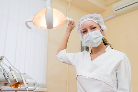 dentalcare: Portrait of a female dentist doctor adjusting a dental lamp, patient point of view