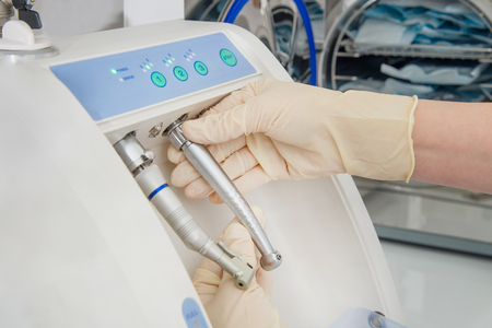 Instrument sterilization and cleaning in dentistry, using automatic instrument maintenance equipment to clean turbines and handpieces, closeup shoot. Stock Photo