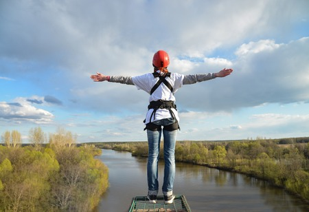 Rope jumping from high altitude of bridge. Woman standing on Platform and ready to make jump.