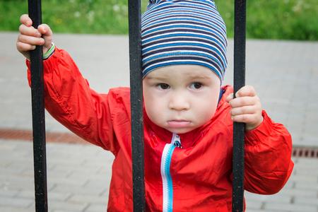 Sad little boy looks through a lattice
