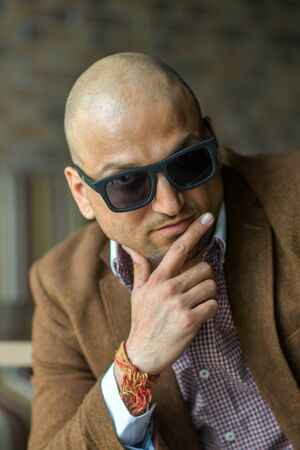 portrait of a hansome indian businessman in sunglasses, serious and confident man