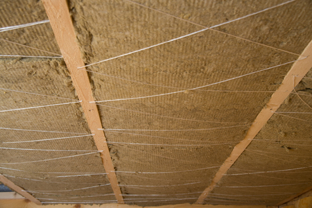 Roof heat isolation with mineral wool in wooden house, building under construction
