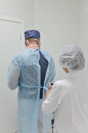 外科手術服、バックにビューを配置する外科医をアシスタントします。