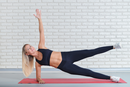 Happy middle aged woman exercising on yoga mat, fitness workout at gym