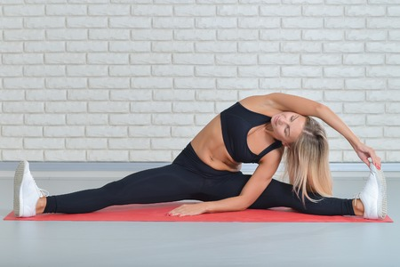 Fitness woman exercising on yoga mat performing twine. Stretching at gym.