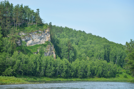Cliff rock at coast of river with forest trees in summer.