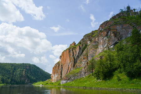 Beautifeul mountain river landscape in bright summer day, scenic rock formation on river bank.