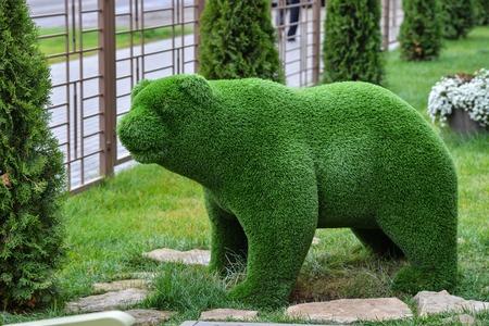 Green grass bear decorative sculpture on the lawn in garden