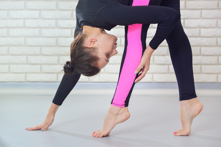 Young elegant woman dancer stretching at gym standing on toe, closeup portrait. Fitness and lifestyle concept.