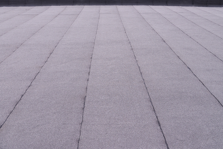Flat surfaced roof coating. Heating and melting bitumen roofing felt background pattern.