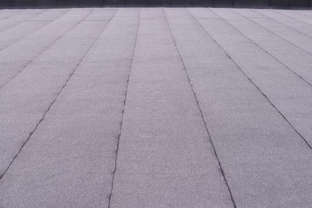 Flat surfaced roof coating. Heating and melting bitumen roofing felt background pattern.
