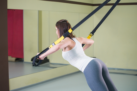 Mujer joven haciendo flexiones de entrenamiento de suspensión con correas de fitness trx, vista lateral