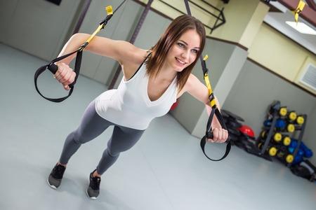 若い幸せな女性は、腕立て伏せを行います。TRXサスペンショントレーニング。