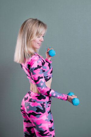 Beautiful blonde girl in pink camouflage sportswear does exercises with dumbbells. Biceps workout. Three quarter length portrait.