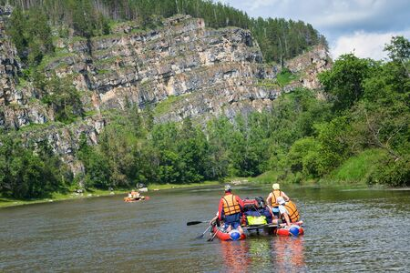 Team of people float down the River on inflatable catamaran among beautiful rocks and mountains of Russia, Bashkortostan, Ay river.