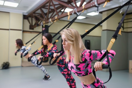 Women group performs pushups with suspension straps, fitness workout at gym, selective focus. Stock Photo