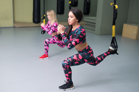 Sporty Women perform exercises with suspension straps, fitness workout at gym, selective focus.